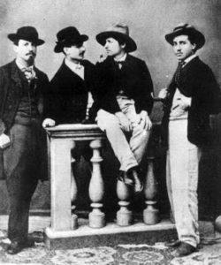 Il pittore Daniele Ranzoni siede sulla balaustra attorniato da alcuni amici della Scapigliatura locale. Tutti rigorosamente con cappelli di varie fogge: c'è o non c'è una magiostrina?